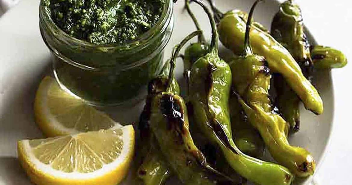 Blistered shishito peppers on a white plate with lemon wedges and citrus pesto dip in a glass jar