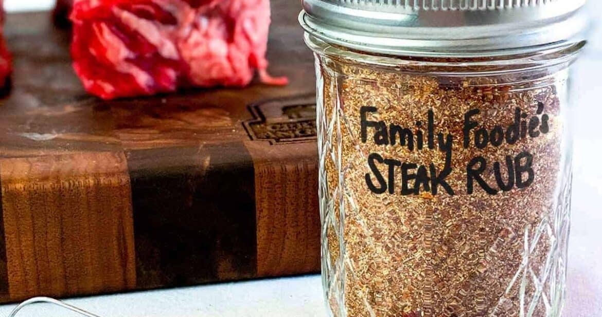 Close up of dry rub recipe in a glass jar in front of a beef short rib on a cutting board with a tiny whisk