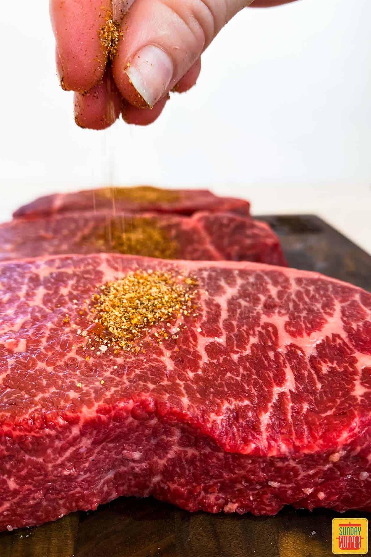 Sprinkling dry rub recipe onto beef short ribs