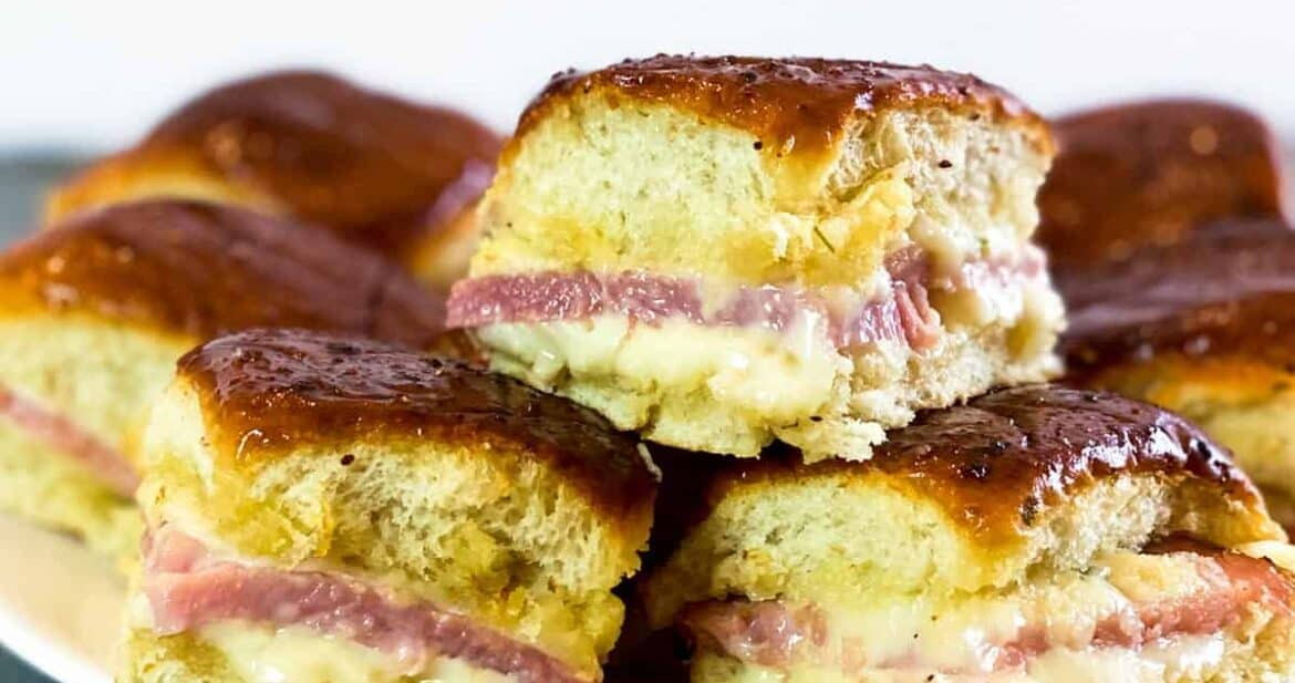 Three leftover ham and cheese sliders on a white plate, stacked on top of each other