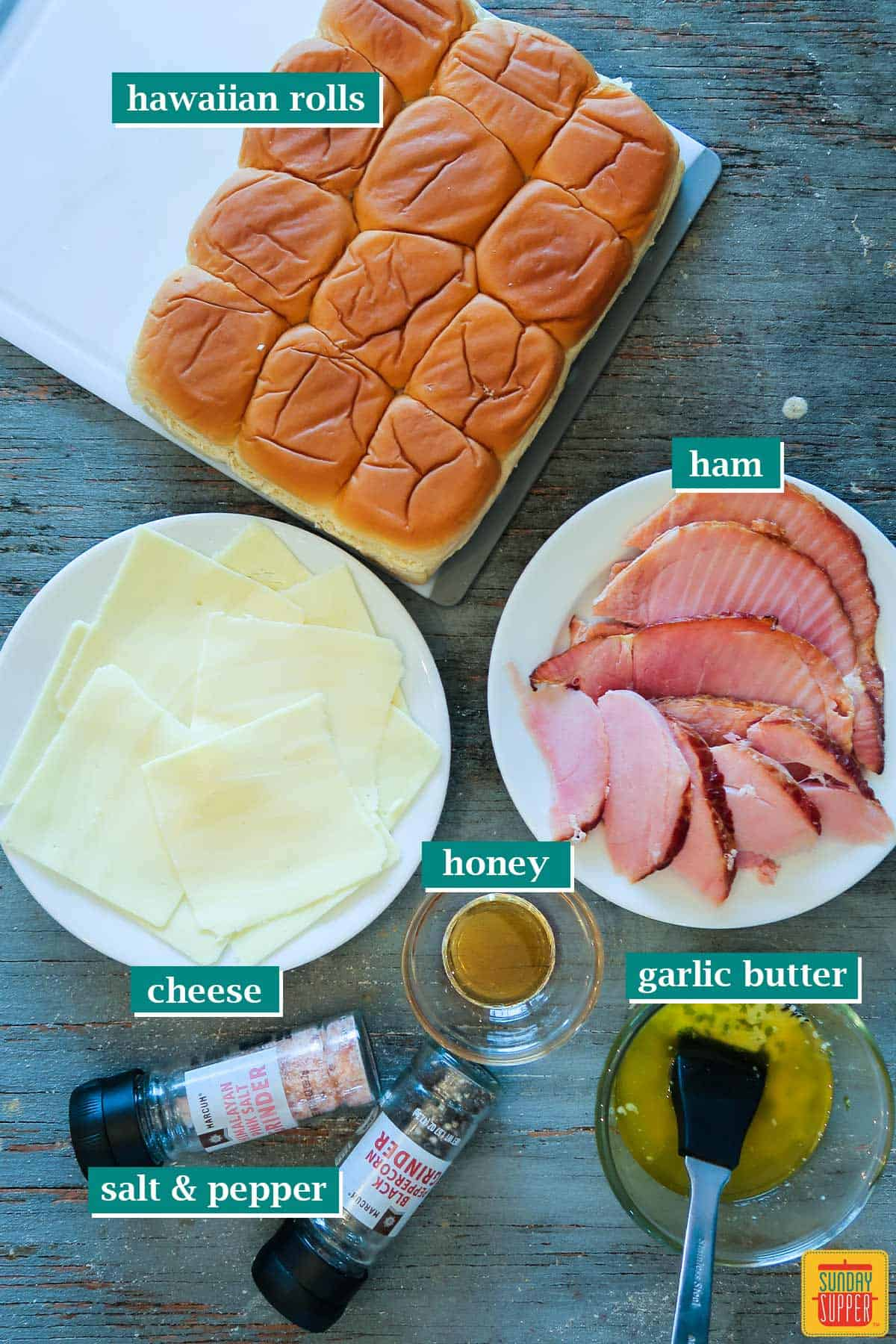 Ingredients to make garlic butter ham and cheese sliders on a wooden surface with labels for each ingredient