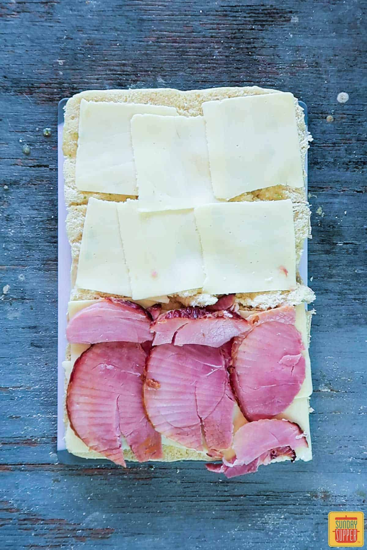Cheese and ham layered onto the slider rolls for ham and cheese sliders