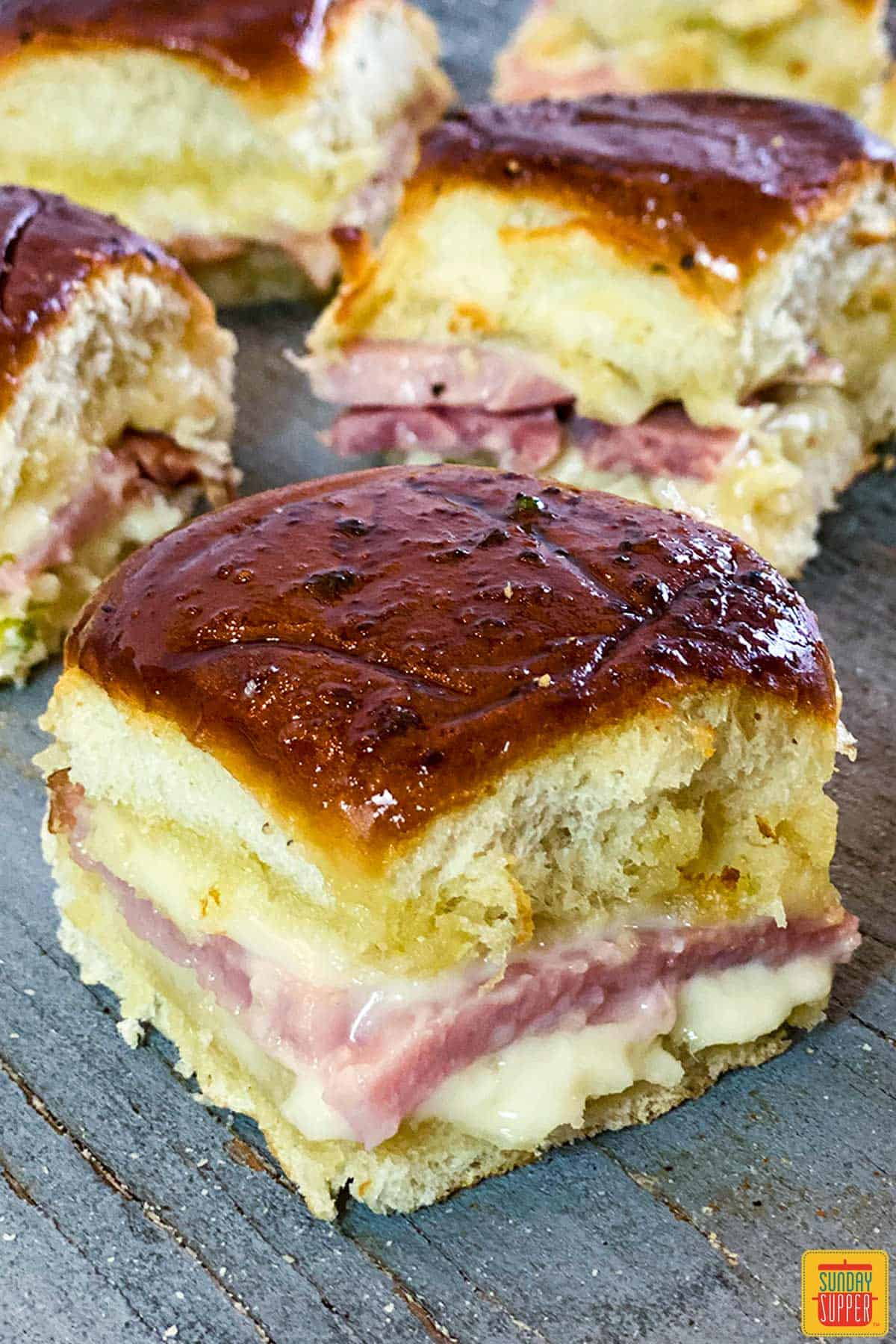 Close up of one garlic butter ham and cheese slider with more visible in the background