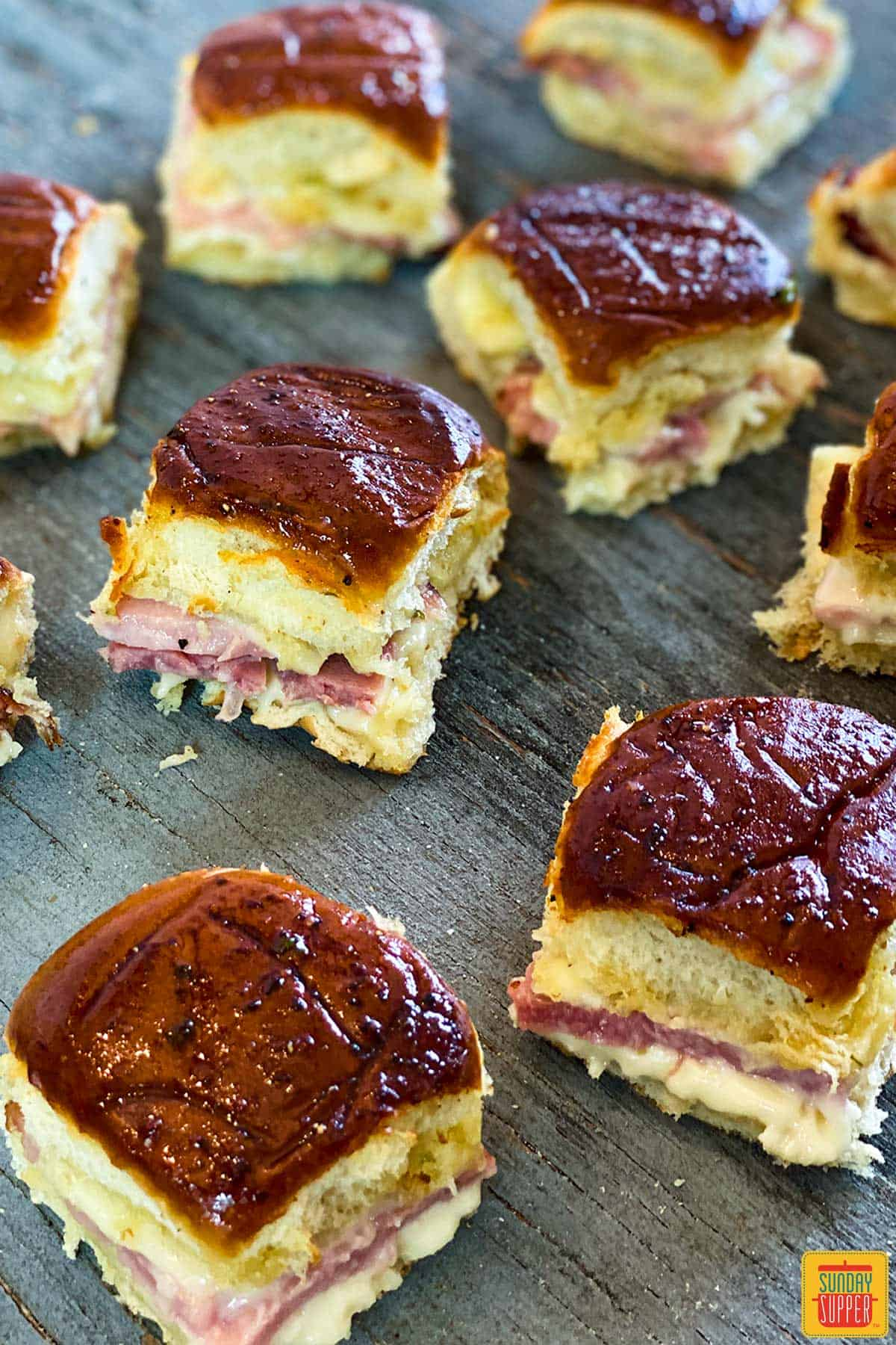 Many ham and cheese sliders on a blue wooden surface with beautifully browned buns