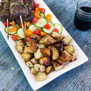 Grilled Potatoes Recipe served on a white platter with Portuguese Beef Skewers and Tomato Cucumber Feta Salad