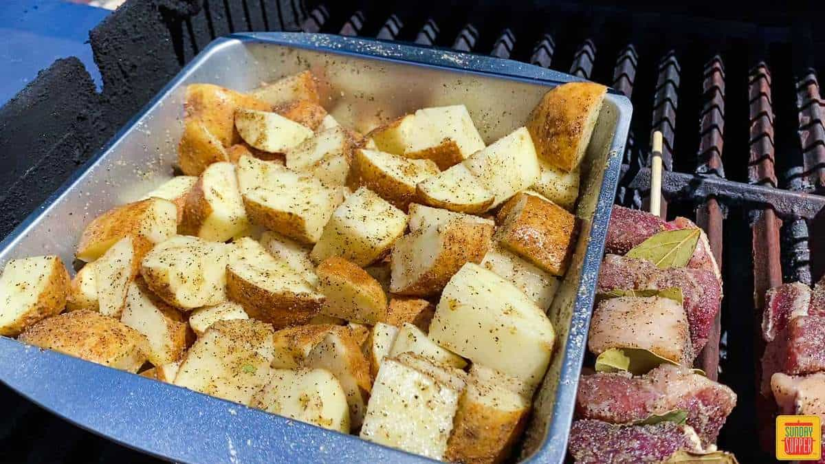 Adding the potatoes to the grill in the baking tin