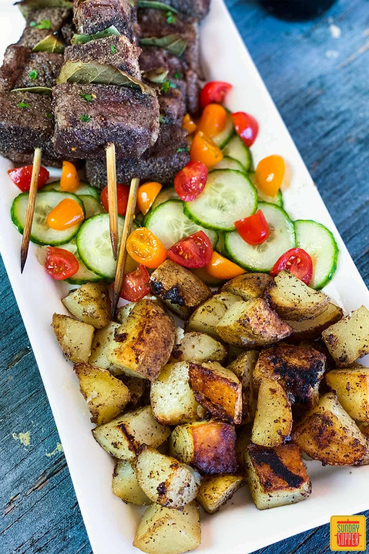Grilled potatoes on a white platter with tomato cucumber salad and Portuguese Beef Skewers