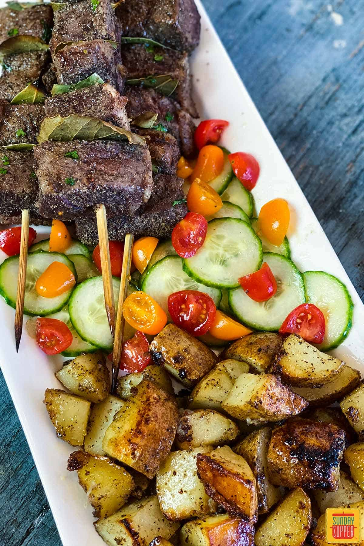 Close up of grilled potatoes recipe after cooking with a side of tomato cucumber salad and Portuguese Beef Skewers