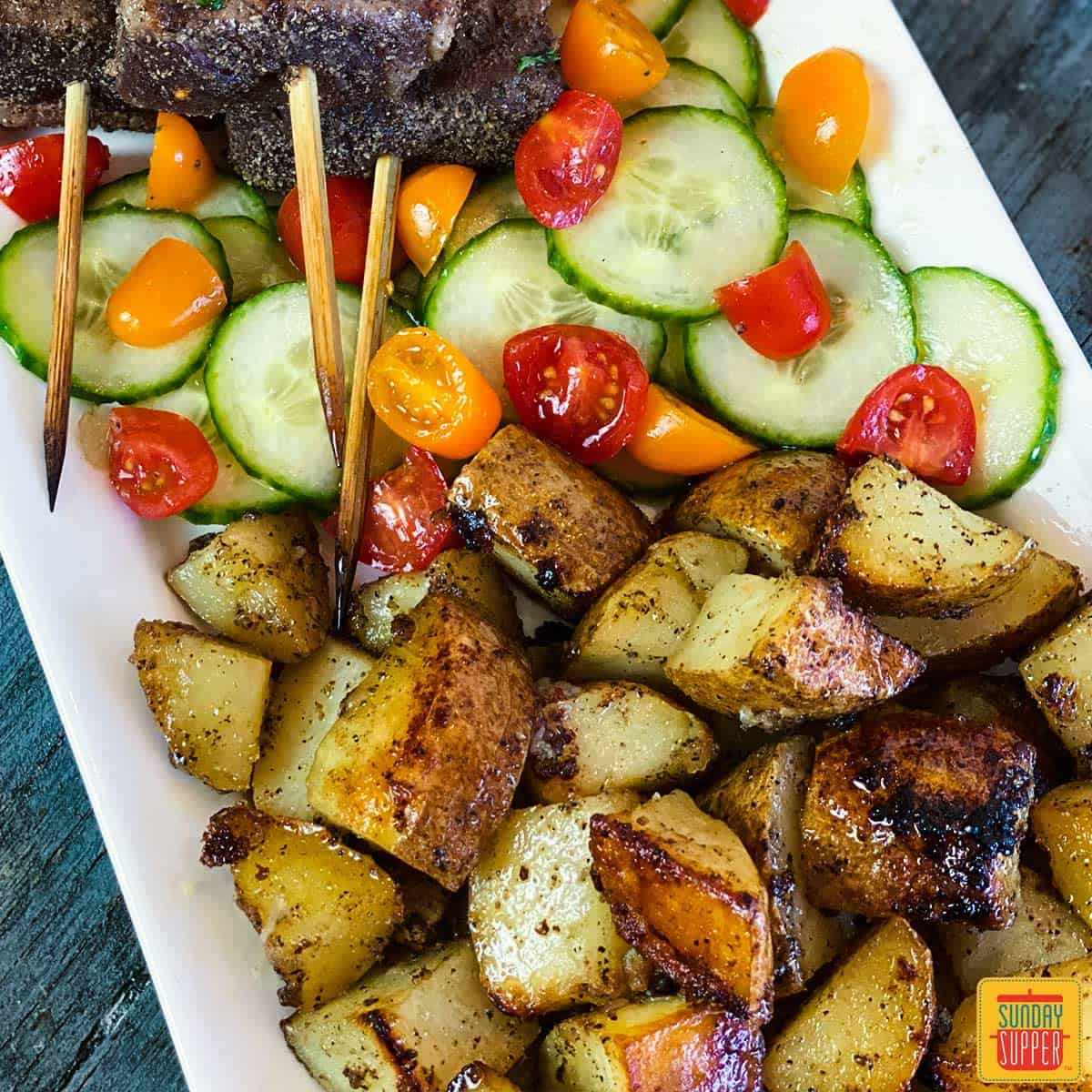 Close up of golden brown, crispy grilled potatoes recipe on a white platter with a side of tomato cucumber salad and Portuguese Beef Skewers just out of shot