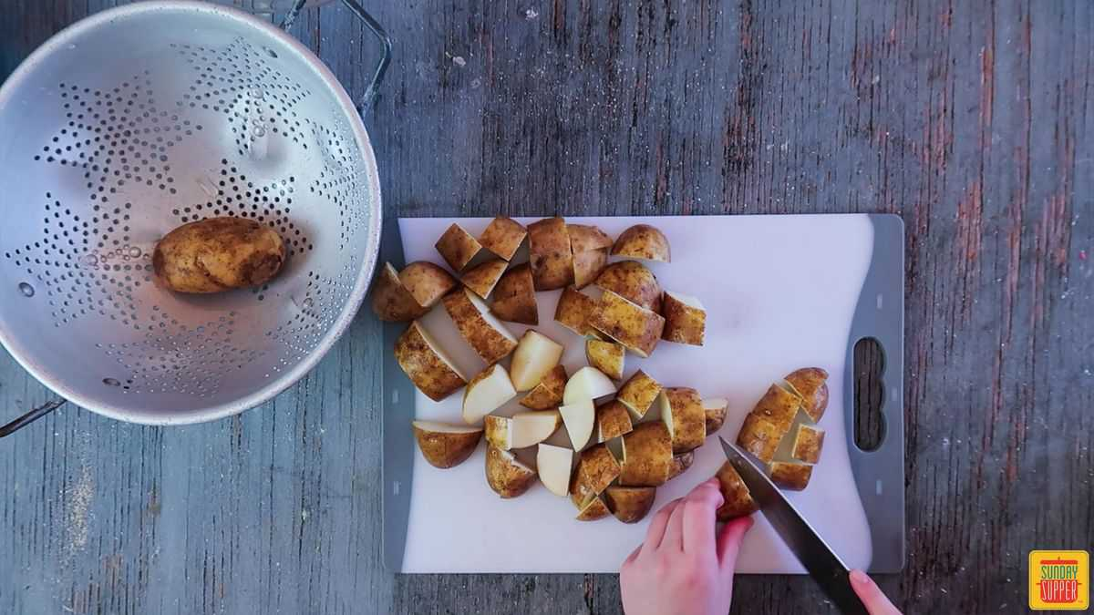 Cutting 5 potatoes into cubes for the grilled potatoes recipe on a white cutting board