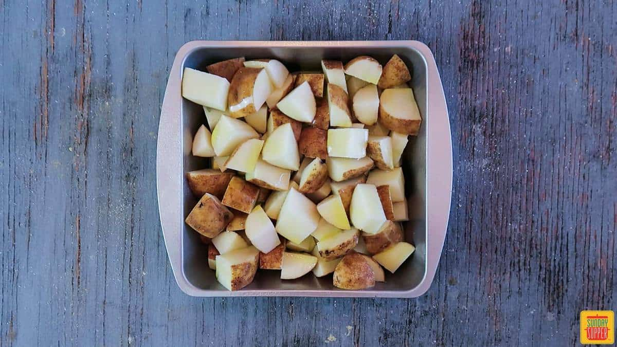 Diced potatoes in a baking tin with olive oil on top for grilled potatoes recipe
