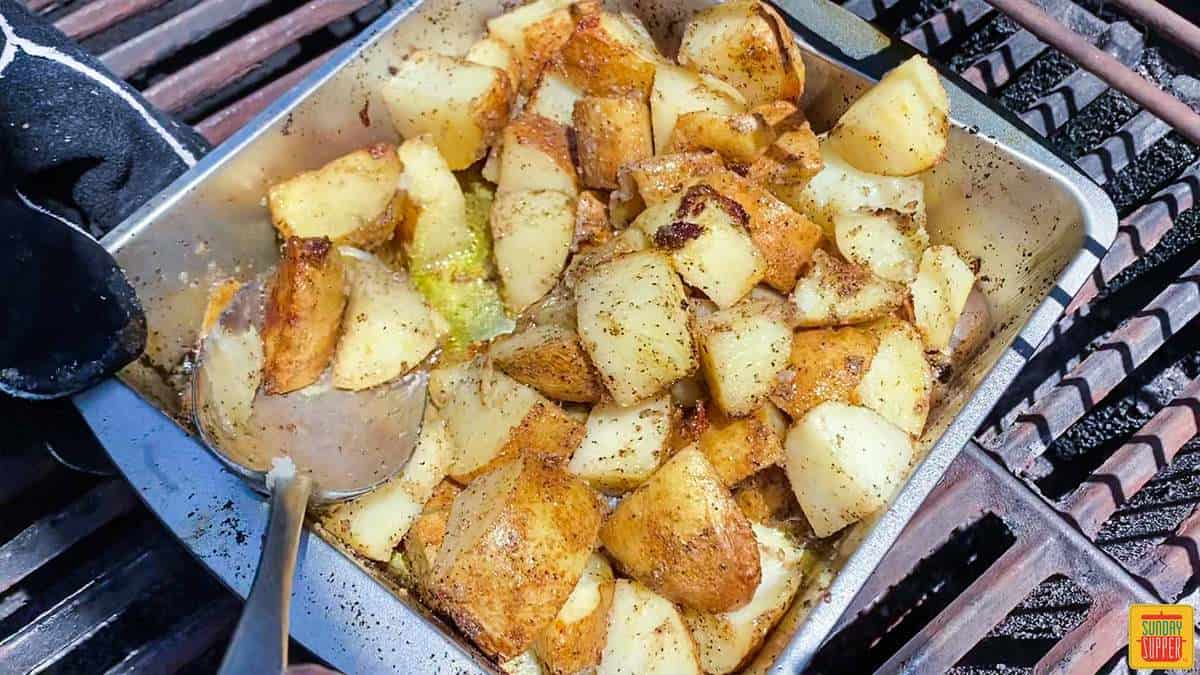 Stirring the grilled potatoes recipe in the baking tin