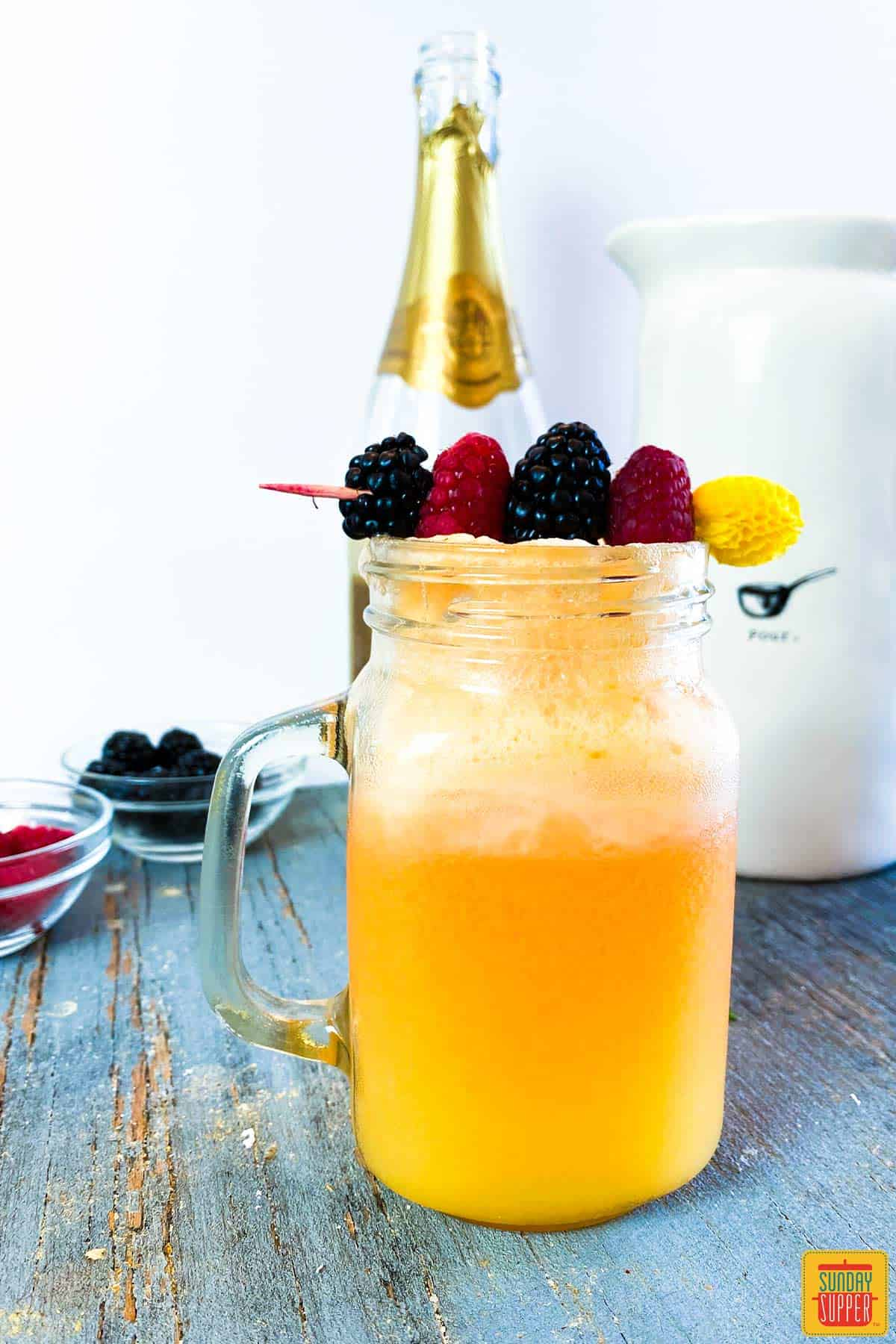 Momosa mimosa recipe in a glass jar with fresh berries and a champagne bottle in the background