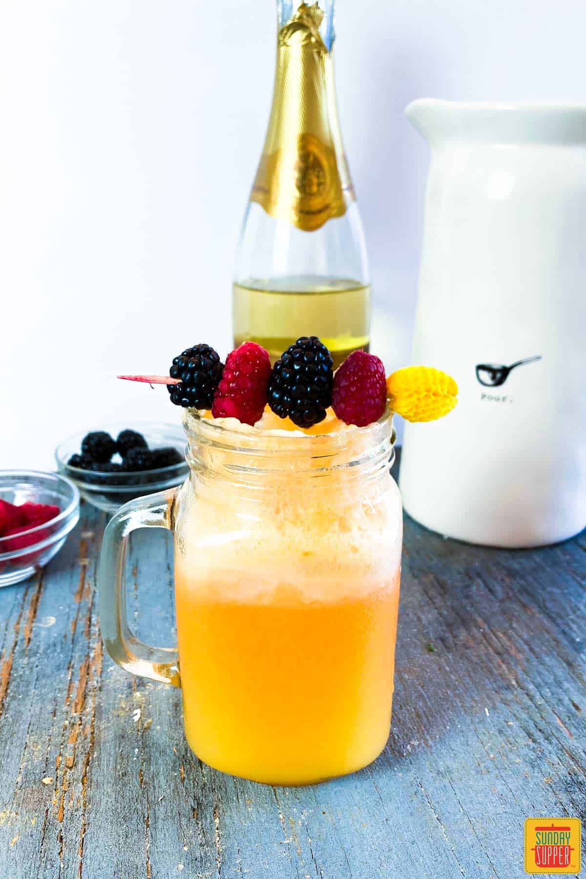 Orange mimosa in a glass jar in front of a champagne bottle and fresh berries in bowls