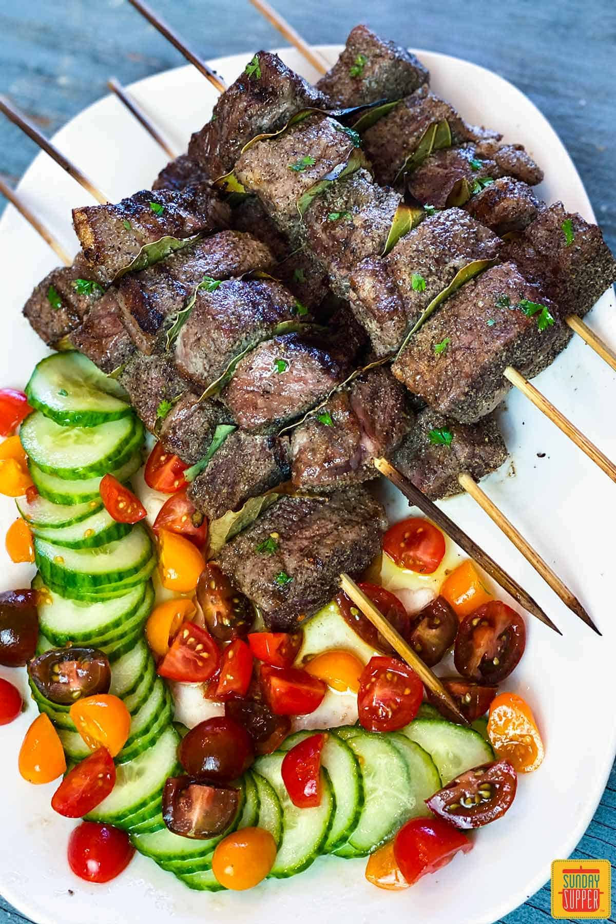 Overhead shot of Portuguese beef skewers on a white platter with tomato cucumber salad on the side