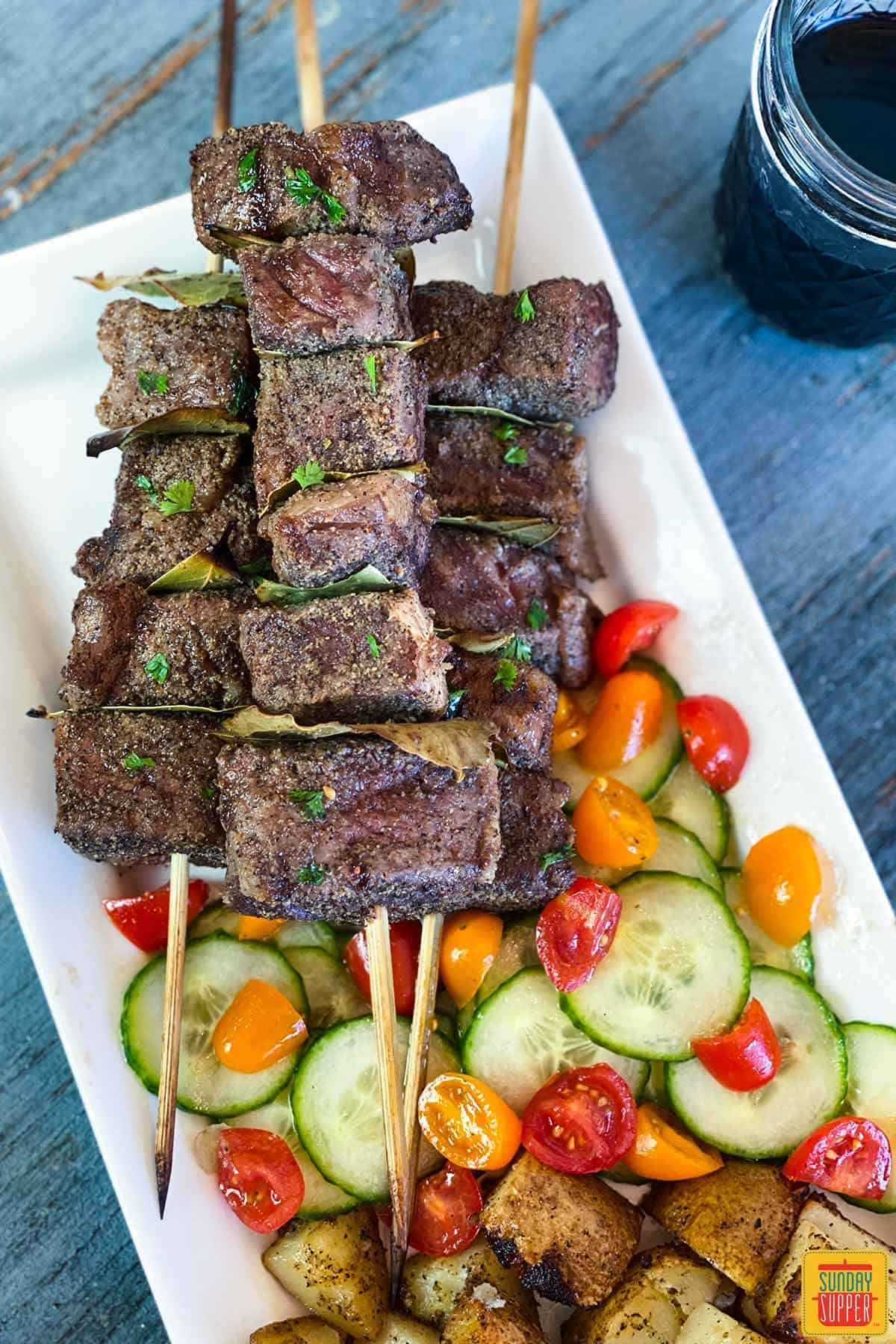 Portuguese beef skewers layered over a bed of cucumbmer tomato salad with grilled potatoes