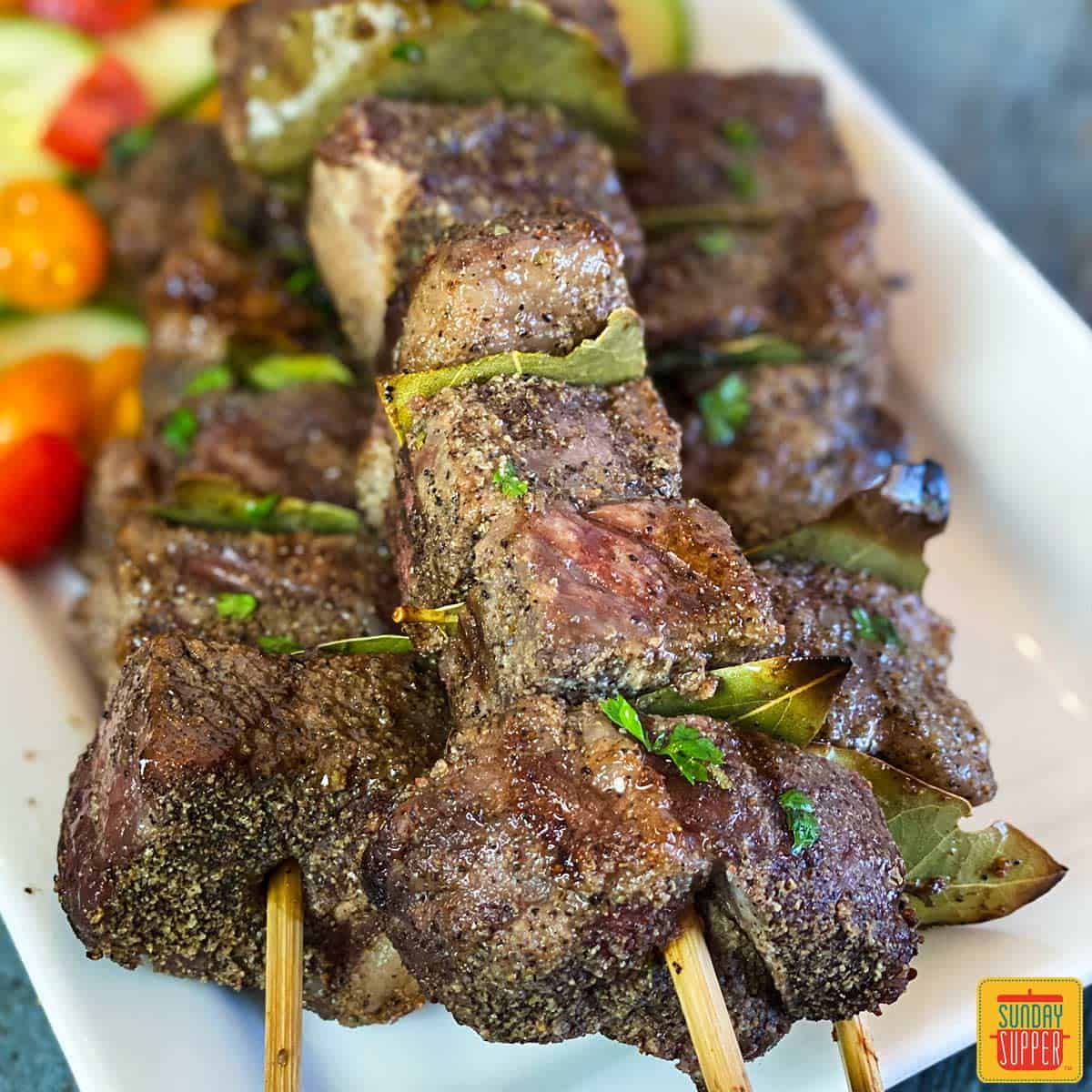 Close up of Portuguese Beef Skewers (Espetadas Madeira) on a white platter with tomato cucumber salad behind the beef