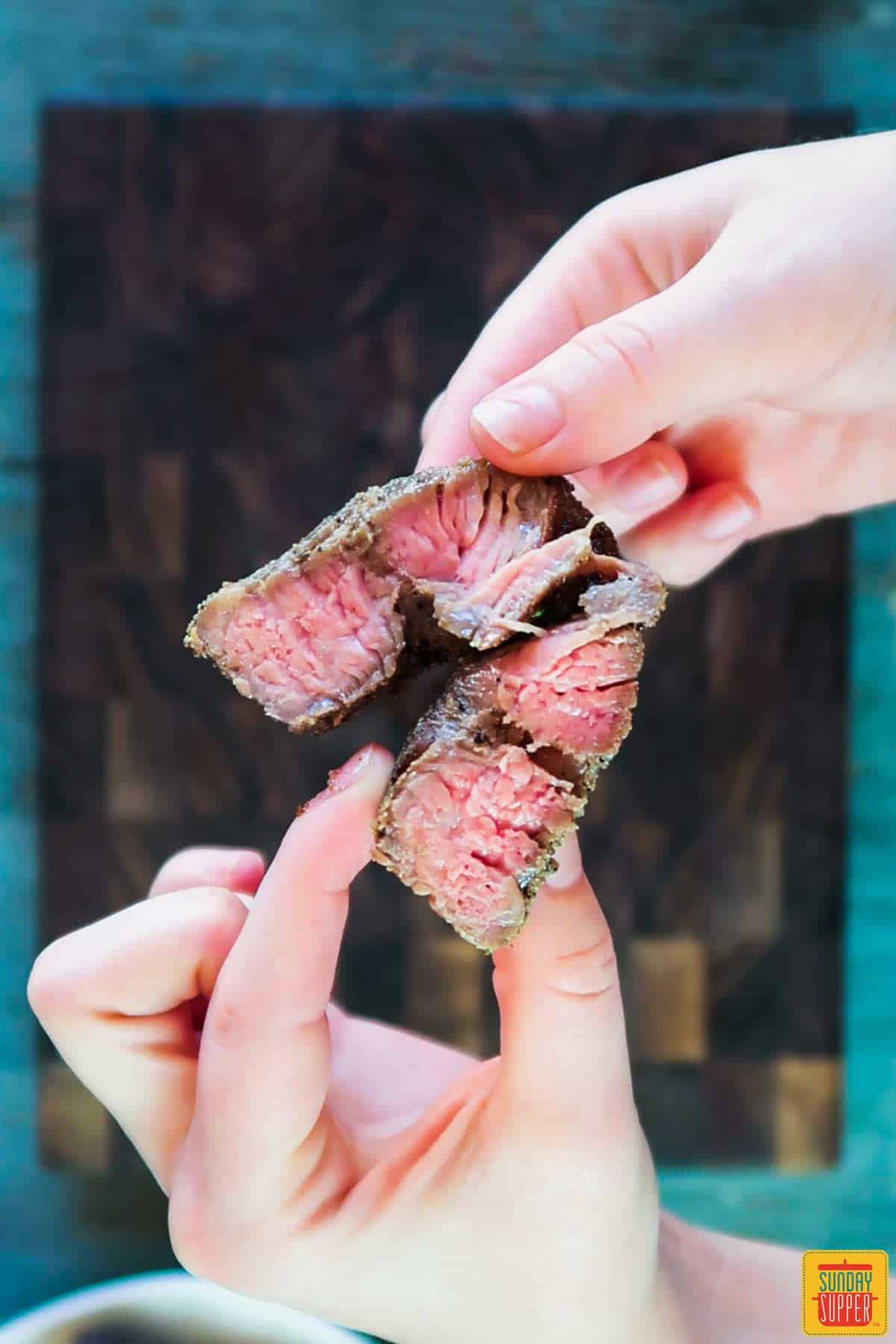 Showing the beautiful pink medium-rare of steak kebabs by splitting a piece with hands