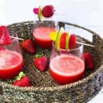 Three glasses of strawberry daiquiri with skewers of fruit on top