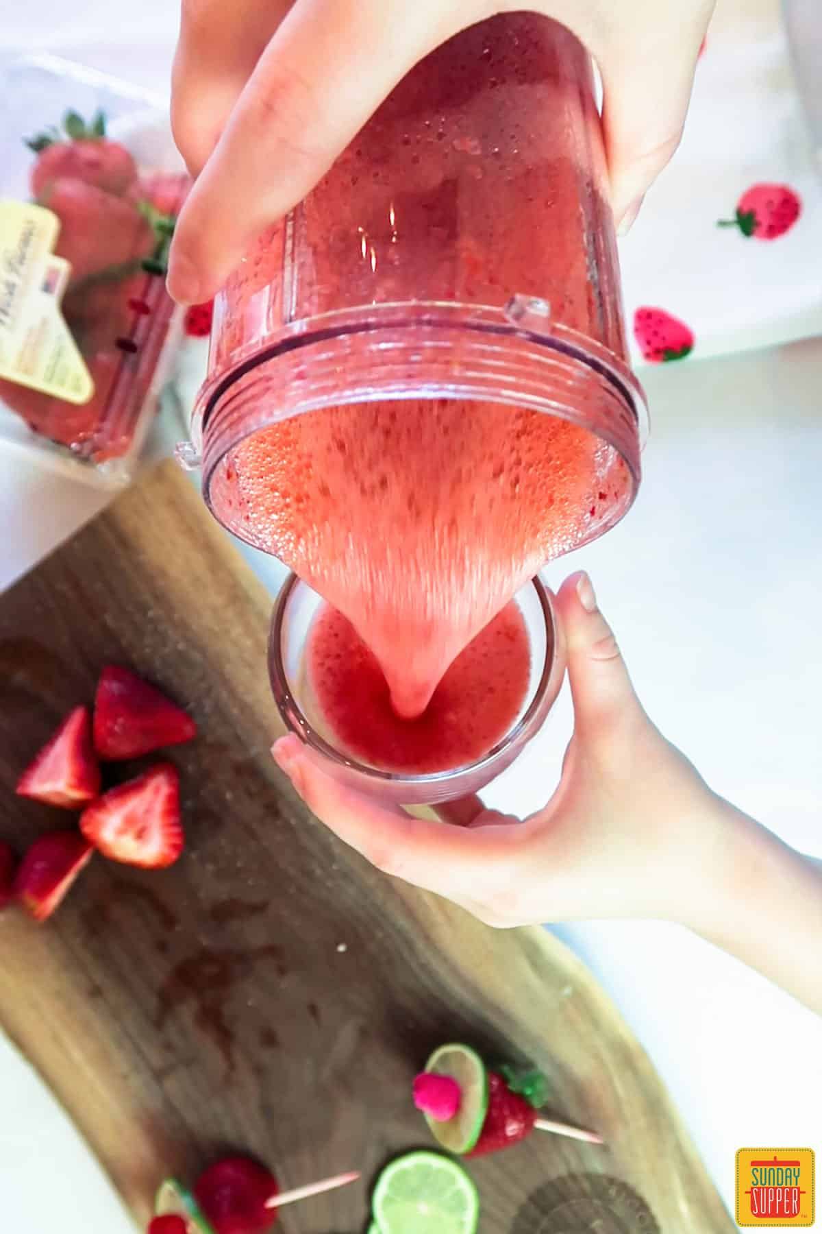 Pouring strawberry daiquiri into a glass cup