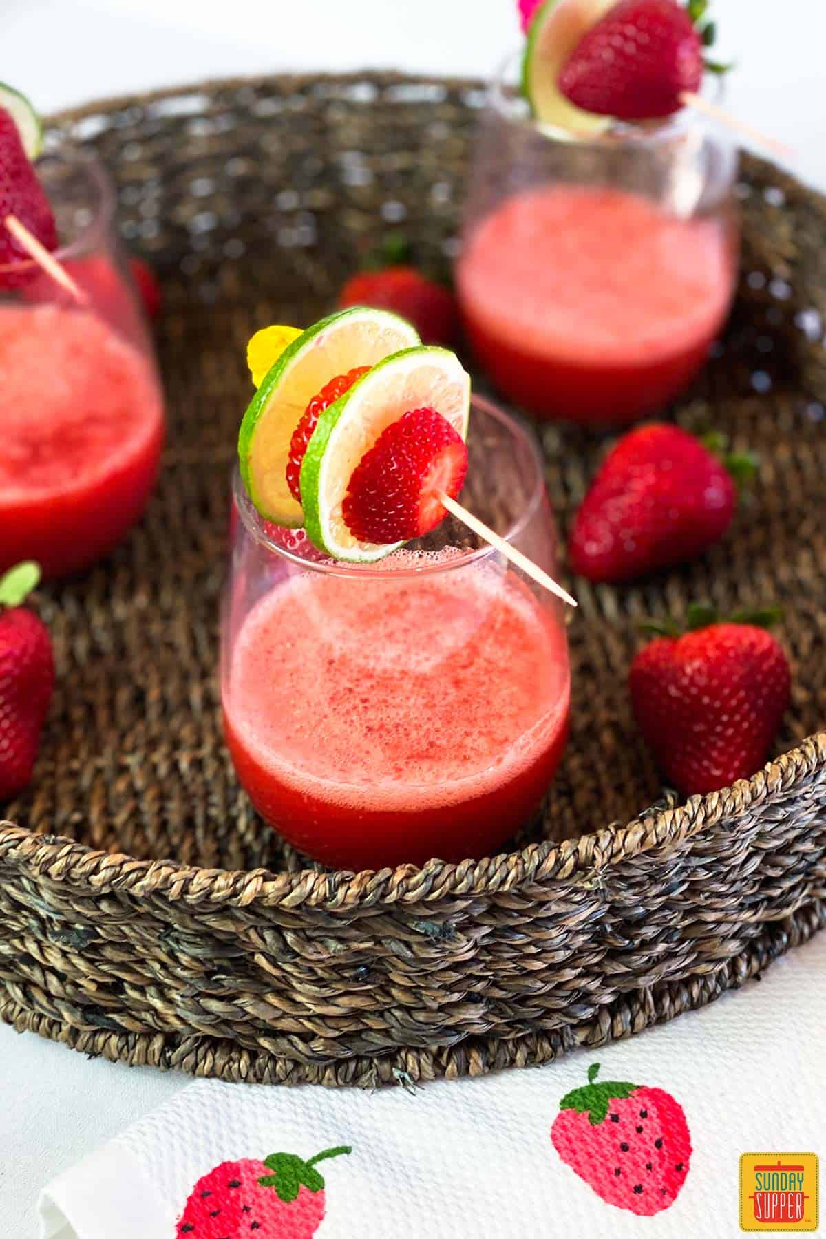 Three glasses of strawberry daiquiri recipe in a flat-bottom round basket with fresh strawberries