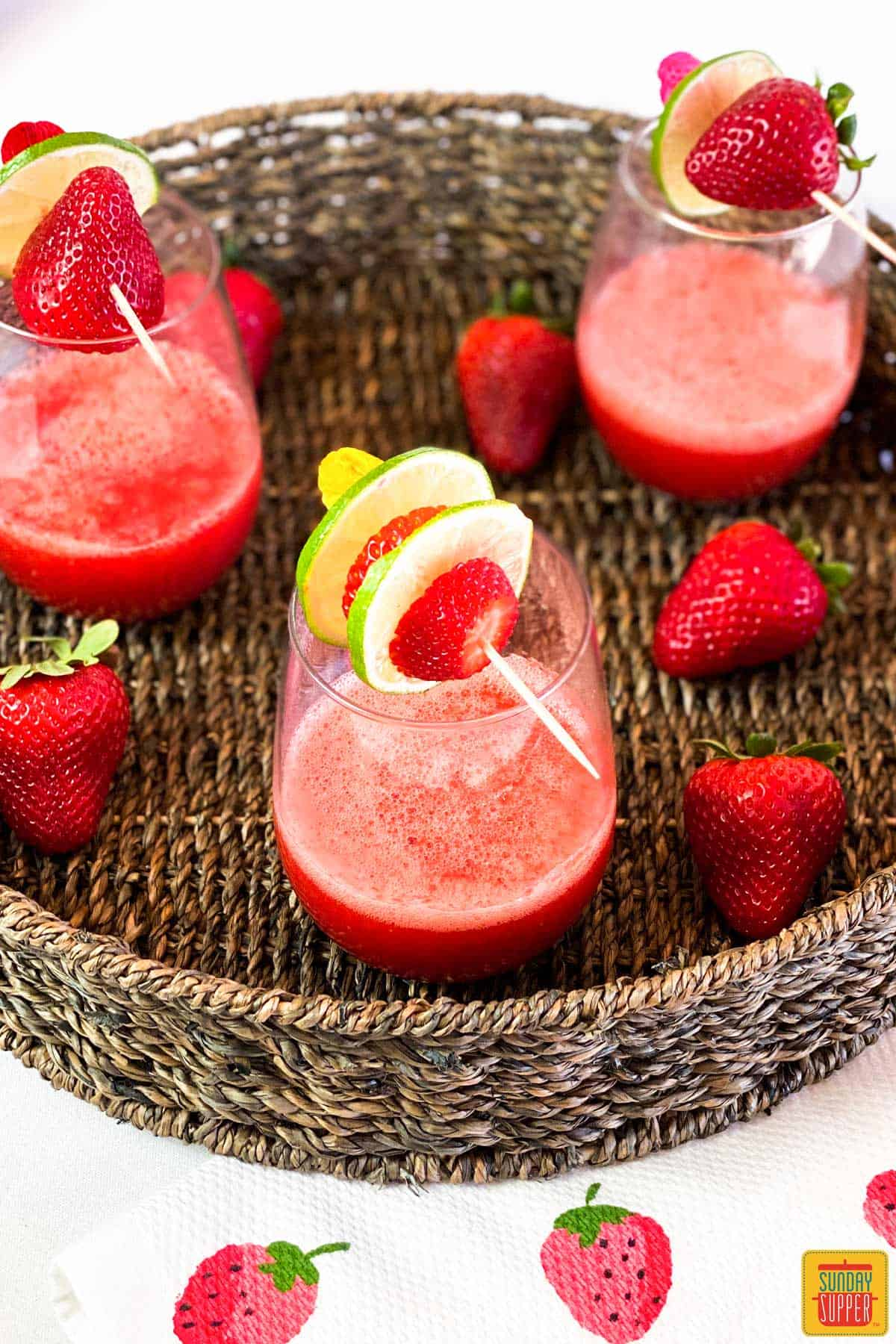 A glass of strawberry daiquiri recipe with fruit skewered on top, fresh berries, and two glasses in the background
