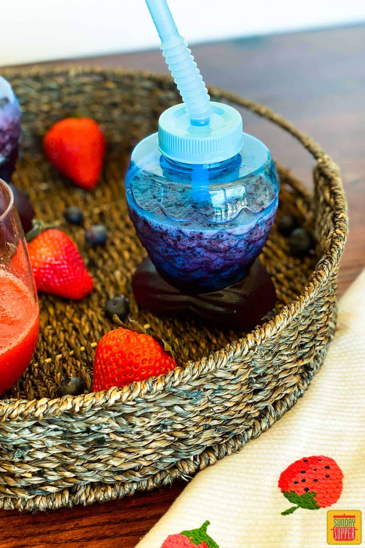 A non-alcoholic frozen strawberry daiquiri recipe using grape juice in a blue fish-shaped cup with a bendy straw, sitting in a flat basket with fresh strawberries