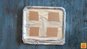 Graham crackers snapped in four halves on an aluminum-foil wrapped air fryer tray in order to make air fryer s'mores recipe
