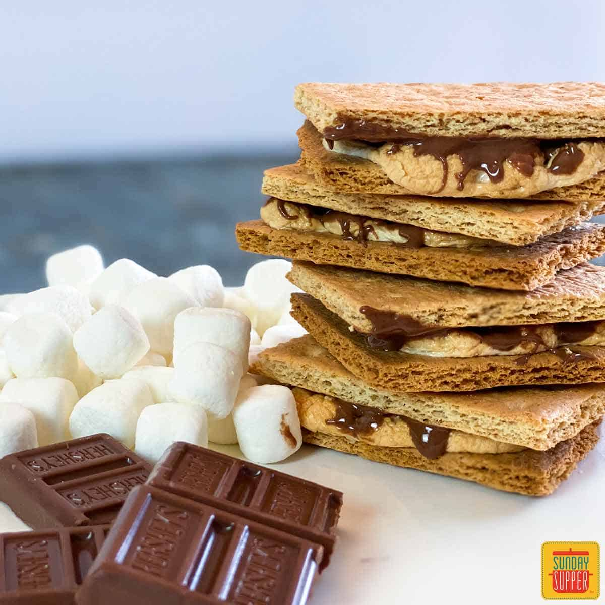 Air fryer s'mores recipe in a stack next to chocolate pieces and mini marshmallows on a white surface