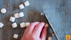 Cutting mini marshmallows in half with a sharp knife
