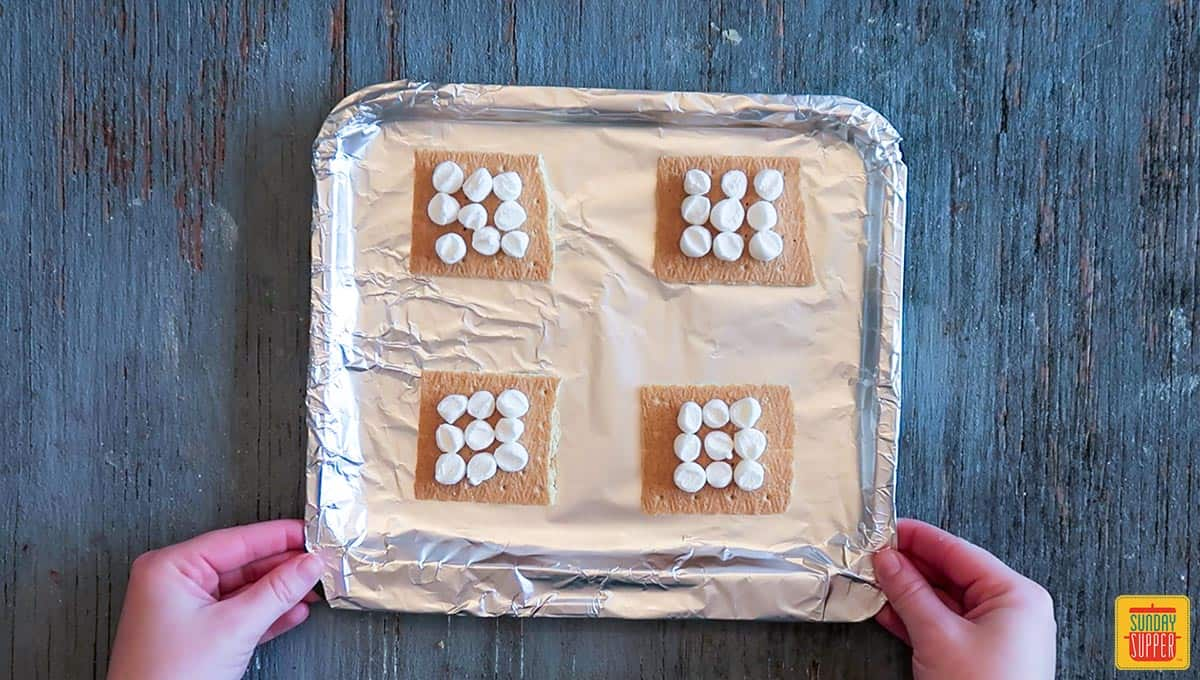 Marshmallows on graham crackers on the air fryer tray wrapped in aluminum foil to make air fryer s'mores recipe