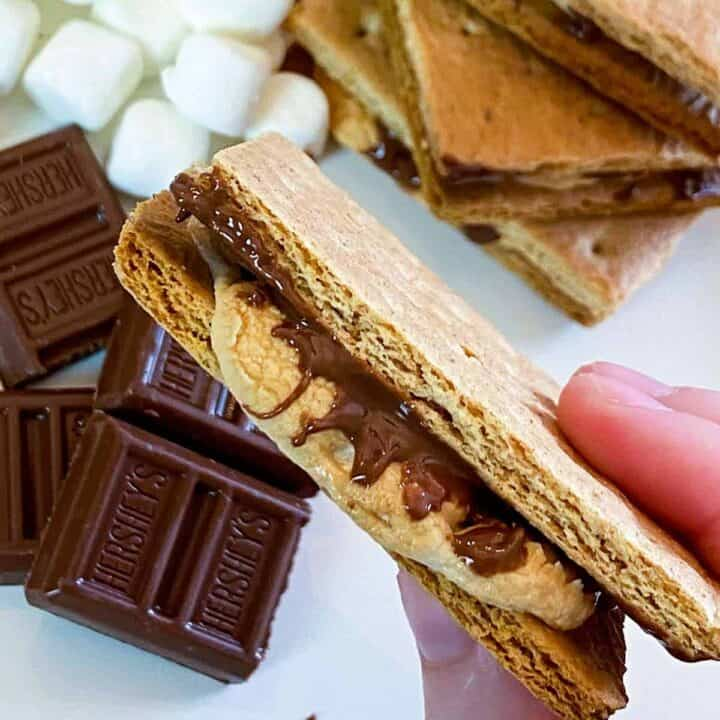 Holding one of the air fryer s'mores over chocolate, marshmallows, and a stack of s'mores