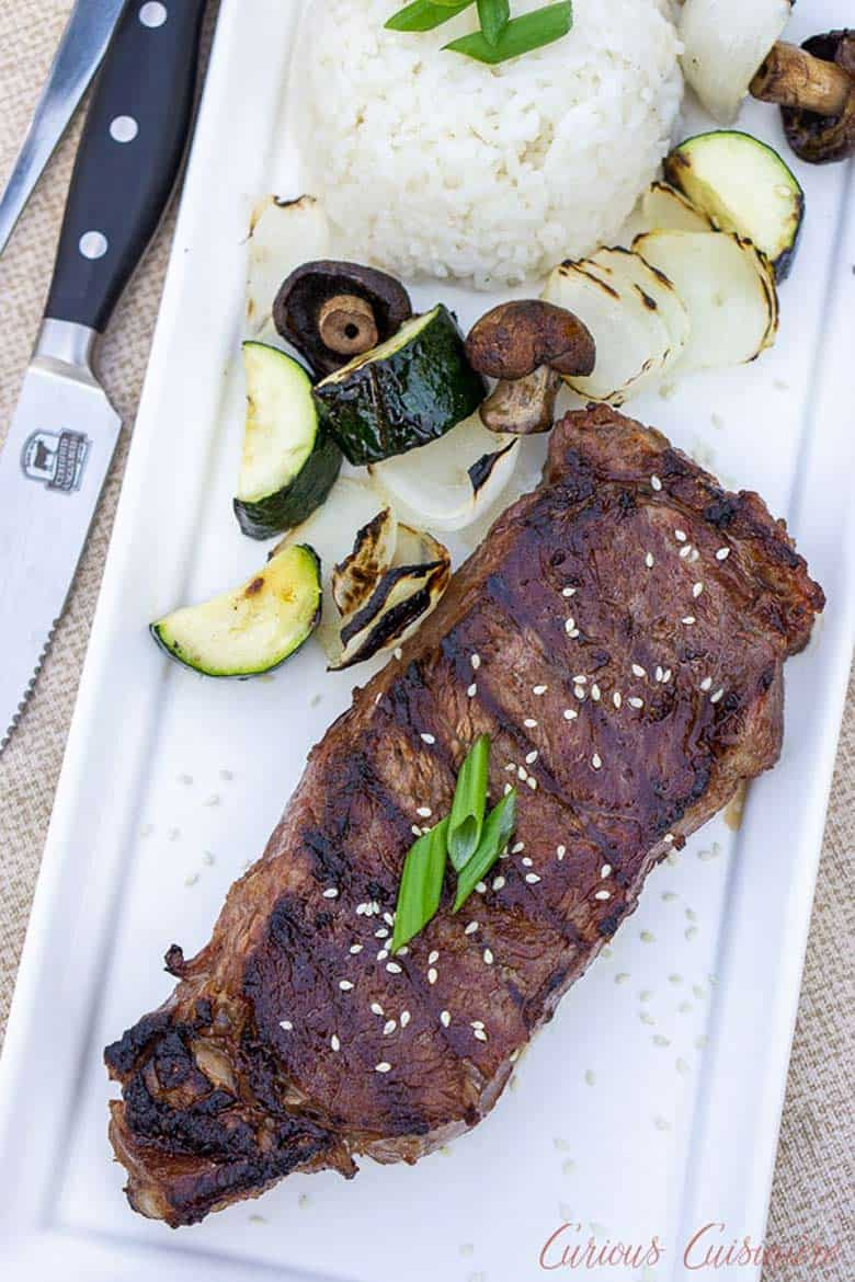 A Japanese grilled hibachi steak on a white rectangular platter with a side of white sticky rice, mushrooms, and sliced grilled zucchini