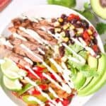 Top-down view of a grilled steak fajita bowl with avocado slices, crema, and lime wedges, next to half an avocado and some more lime wedges