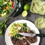 Grilled steaks with creamy poblano sauce on a white plate with a knife surrounded by guacamole, limes, and a salad on a table