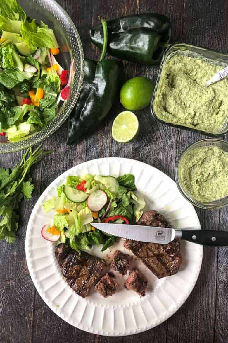 Grilled steaks with creamy poblano sauce on a white plate with a knife surrounded by poblano sauce, whole poblano peppers, limes, and a salad on a table