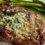 Ribeye steak on a white plate with asparagus and garlic butter melted on top