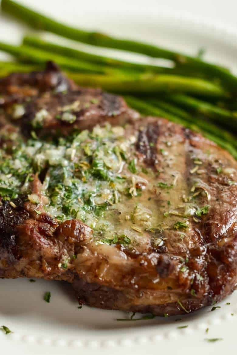 Ribeye steak on a white plate with a side of asparagus and garlic butter melted on top