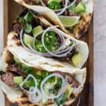 Three honey lime steak tacos topped with sliced red onions, avocado, and lime wedges on grilled tortillas resting on a cutting board