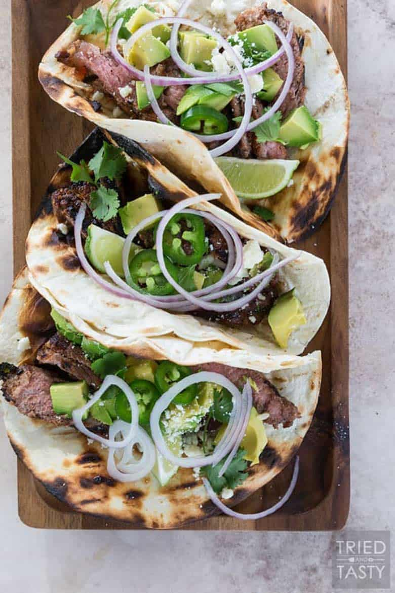 Three honey lime steak tacos topped with sliced red onions, avocado, and lime wedges in grilled tortillas resting on a cutting board