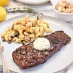 A grilled strip steak on a white plate with pasta salad on the side topped with herb compound butter