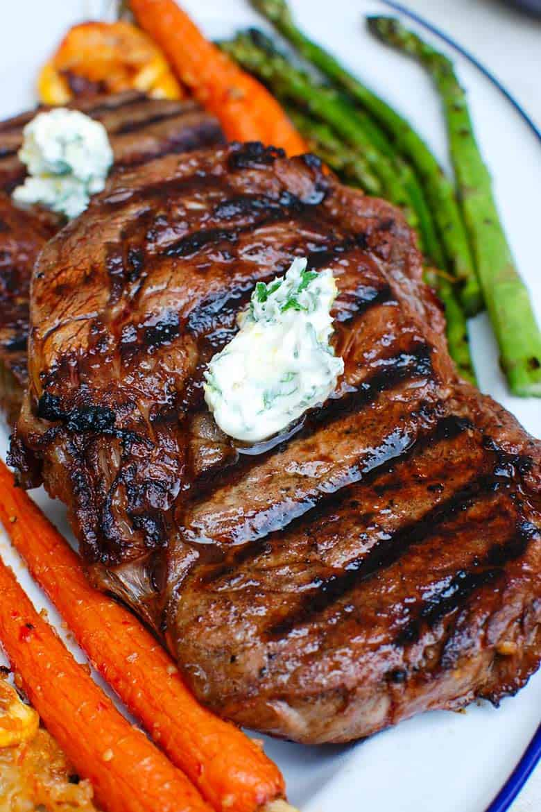 Close up of two lemon garlic butter grilled ribeyes on top of each otheer on a plate with asparagus and whole cooked carrots on the side