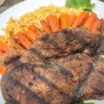 Close up of a Morrocan spiced grilled steak on a plate with carrots, rice, and herbs