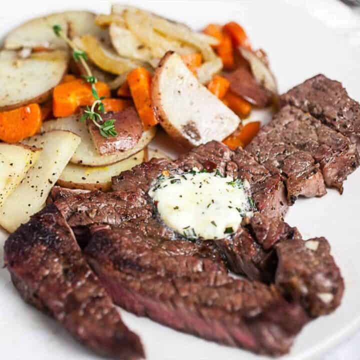 Grilled chuck steak on a white plate topped with garlic butter with a side of potatoes and carrots