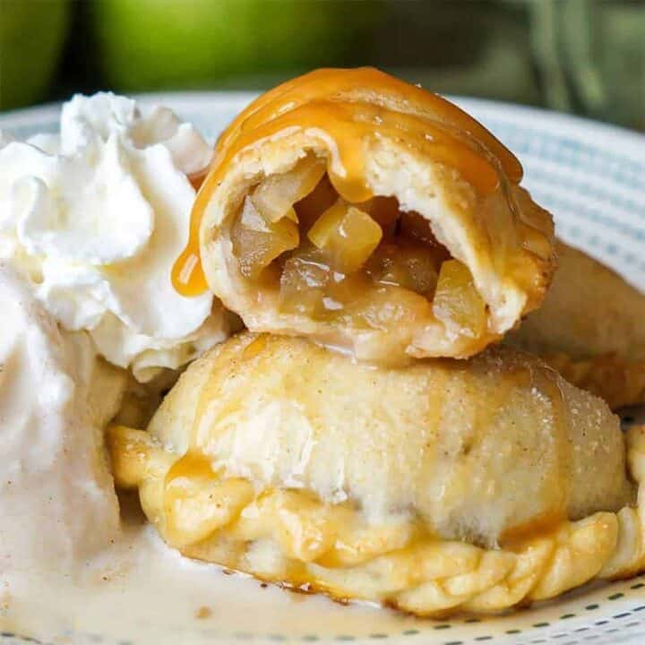 Three caramel apple empanadas up close next to ice cream and whipped cream: the empanada at the top of the stack is cut in half so you can see the apple filling