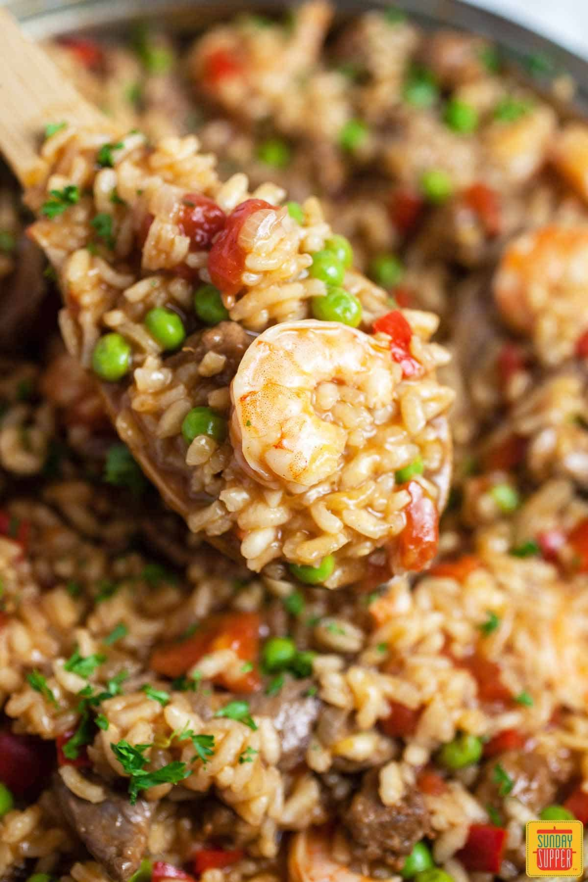 Close up of a wooden spoonful of Spanish rice with a shrimp on top