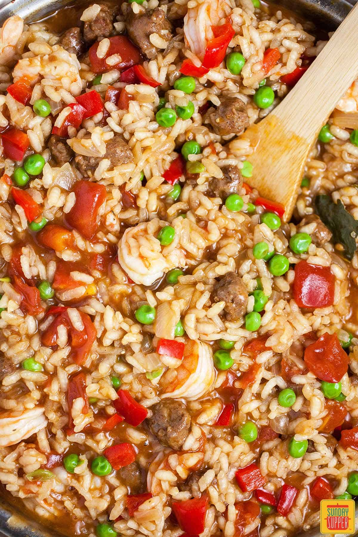 Stirring the shrimp and peas into the easy paella recipe in a skillet, close up