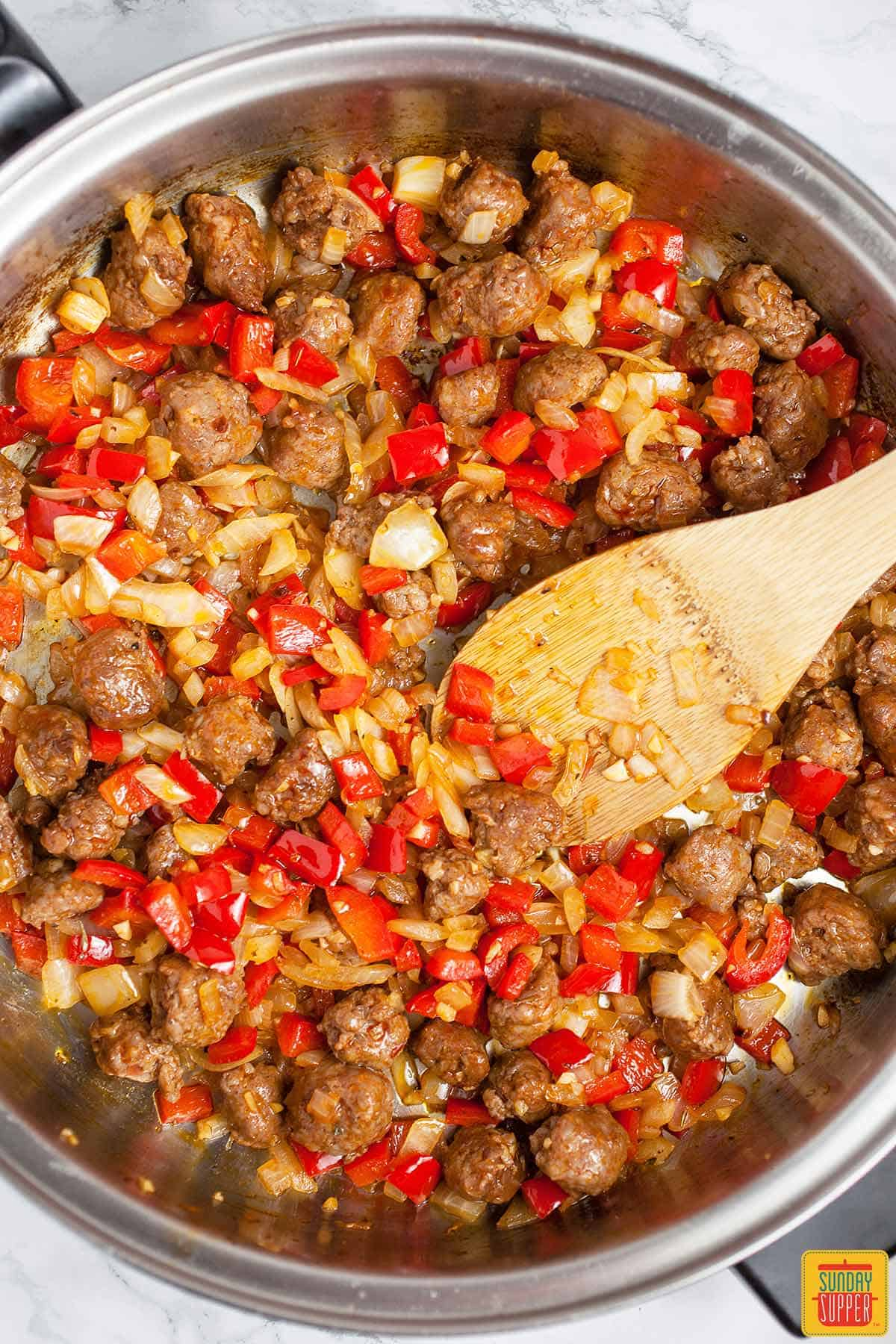Stirring onions, red peppers, and chorizo in a skillet with a wooden spoon for easy paella recipe