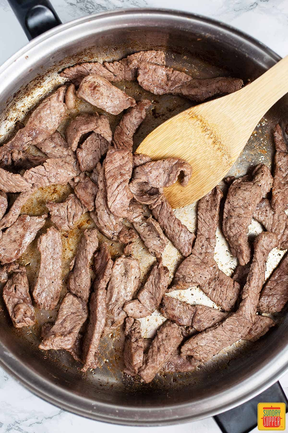 Searing sirloin steak strips for easy  paella recipe with a wooden spoon in a skillet