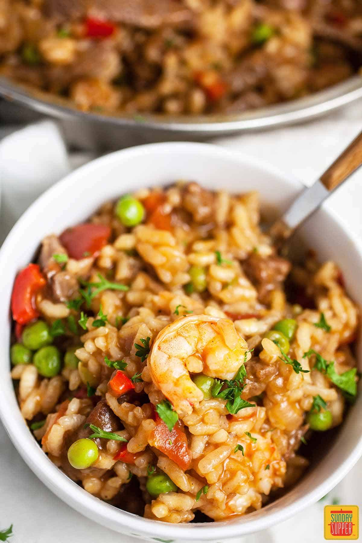 Close up of complete beef and shrimp paella in a white bowl with a fork and shrimp on top